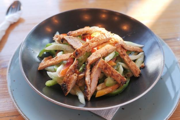 그릇에 테이블에 구운 닭고기와 신선한 야채 샐러드 프리미엄 사진