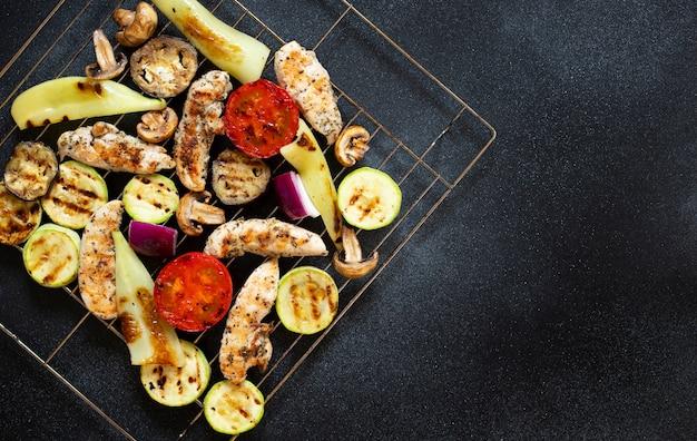 구운 닭고기와 야채, 토마토, 고추, 양파, 가지와 호박. 건강한 다이어트 음식. 건강한 저녁. 저지방 함량. 상위 뷰, 검정색 배경, 복사 공간 프리미엄 사진