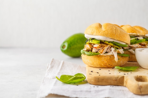 Grilled chicken and avocado burger on wooden board, copy space. Premium Photo