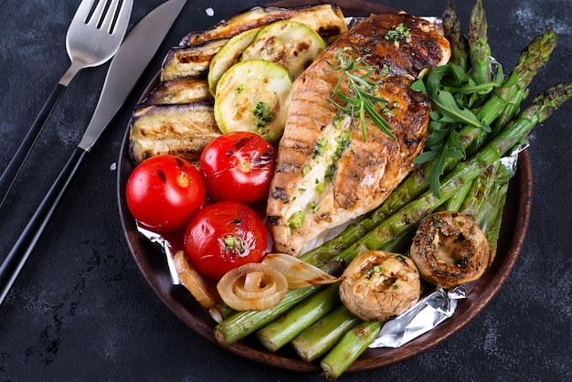 Grilled chicken breast on a cast iron skillet with grill vegetables and green sauce on a stone, flat lay Premium Photo