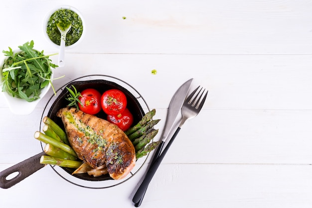 Grilled chicken breast on a cast iron skillet with grill vegetables and green sauce on a white, flat lay Premium Photo