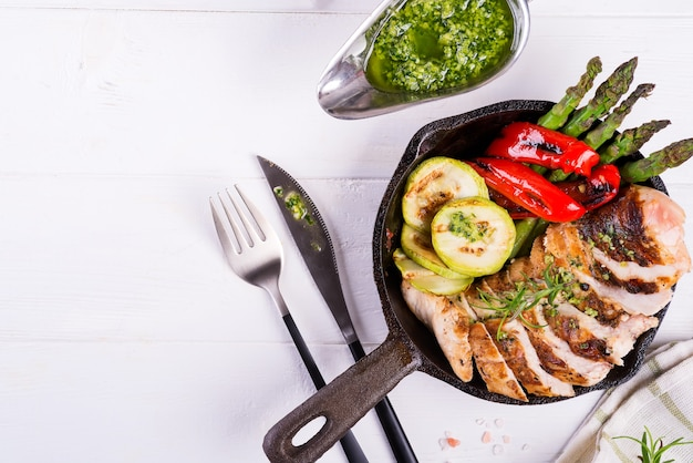 Grilled chicken breast on a cast iron skillet with grill vegetables on wood Premium Photo