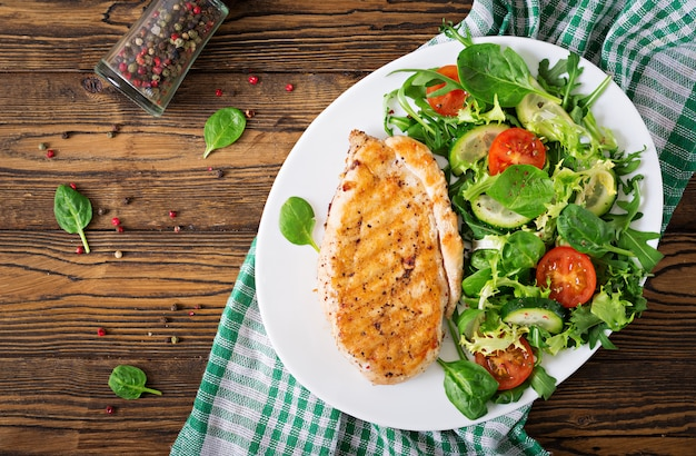 Grilled chicken breast and fresh vegetable salad - tomatoes, cucumbers and lettuce leaves. chicken salad. healthy food. flat lay. top view Free Photo