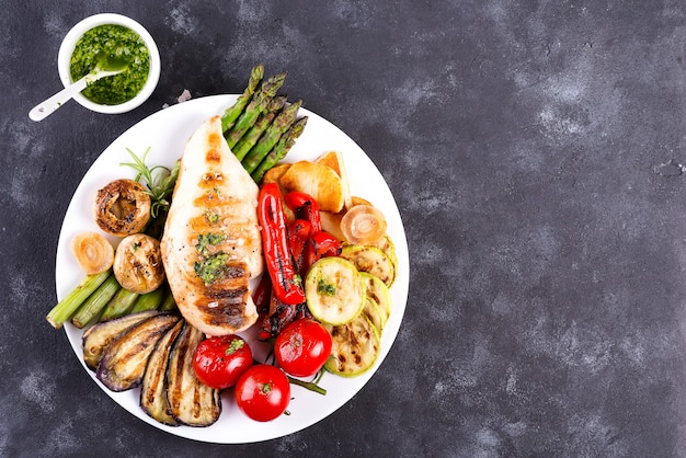 Grilled chicken breast on a plate with tomatoes, asparagus and mushrooms on a stone, flat lay Premium Photo