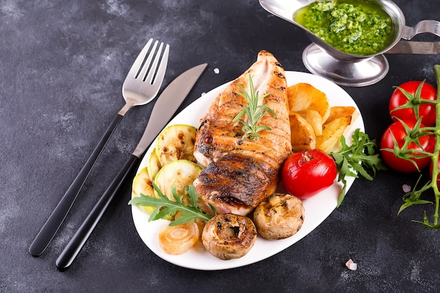 Grilled chicken breast on a plate with tomatoes, mushrooms and green sauce on a stone, flat lay Premium Photo
