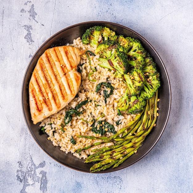 玄米、ほうれん草、ブロッコリー、アスパラガス、食事療法の概念、健康的な食事と鶏胸肉のグリル。 Premium写真
