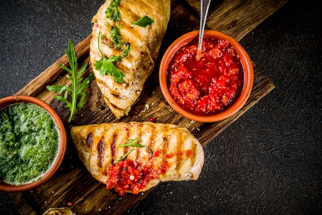 Grilled chicken breast with spicy sauces, tomatoes and herbs Premium Photo