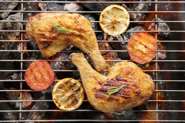 Grilled chicken leg over flames on a barbecue Premium Photo