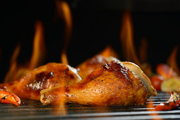 Grilled chicken leg on the flaming grill Premium Photo