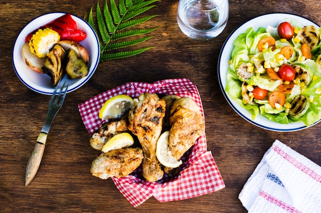 Grilled chicken legs with lemon and salad Free Photo