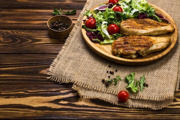 Pollo alla griglia e insalata vicino pepe nero Foto Gratuite
