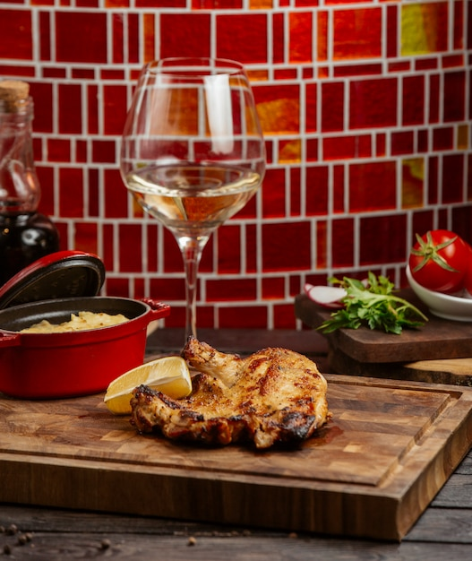 Grilled chicken served with lemon and mashed potato pot on wood board Free Photo