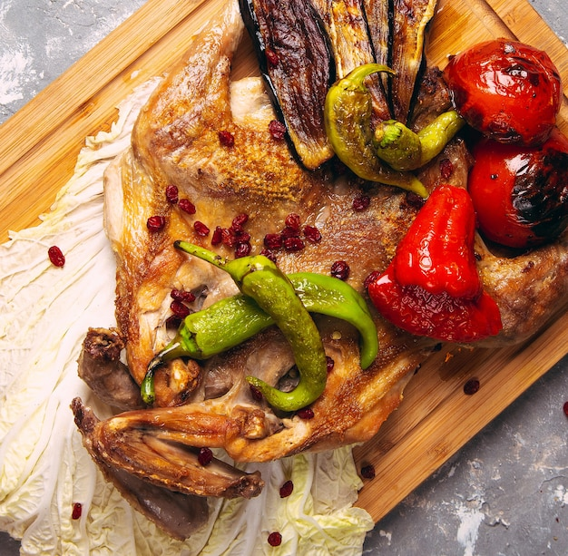 Grilled chicken and vegetables on the wooden board close-up. horizontal view from above Free Photo