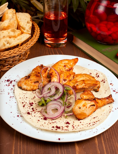 Grilled chicken wings kebab served with composto, onion vegetable salad and herbs in white plate. Free Photo