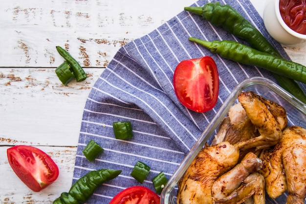 Grilled chicken wings and slices of tomatoes; green chilies on wooden table Free Photo