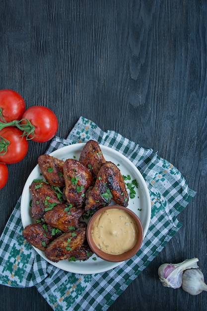 Grilled chicken wings with sauce and herbs.baked chicken wings in pan. Premium Photo