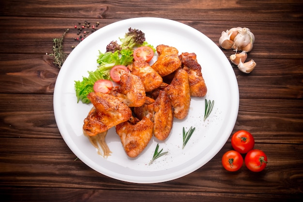 Grilled chicken wings with vegatables and seasoning on a wooden background Premium Photo