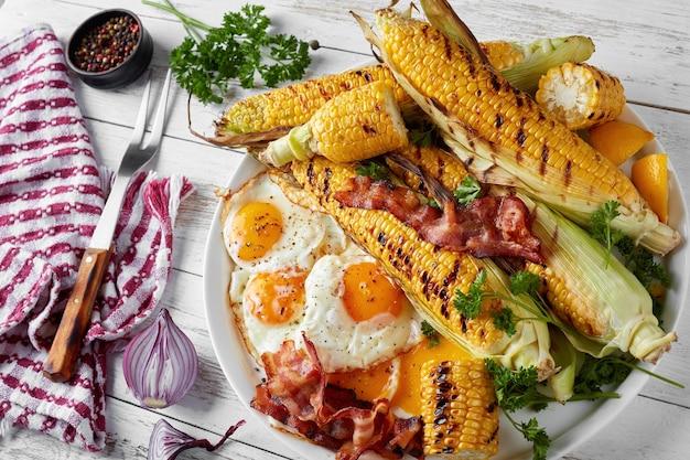 냅킨과 포크, 위에서 가로보기, 근접 오래 된 시골 풍 테이블에 흰 접시에 튀긴 계란과 베이컨 조각과 Cobs에 구운 옥수수 프리미엄 사진