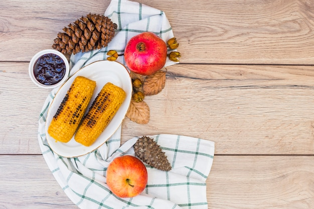 Grilled corns with cones on wooden table Free Photo