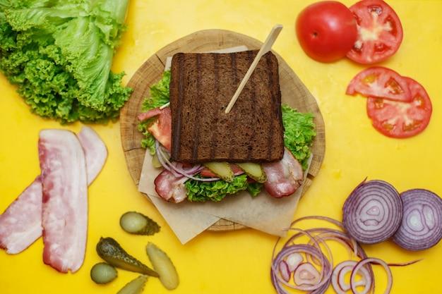 Grilled dark bread sandwich on wooden plate on yellow board Premium Photo