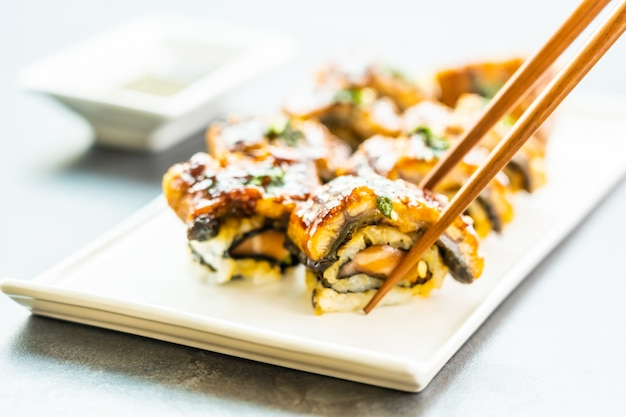 Grilled eel or unagi fish sushi maki roll with sweet sauce Free Photo