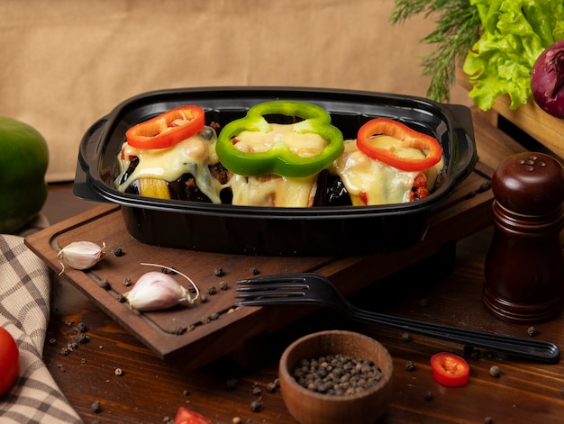 Grilled eggplant slices stuffed with meat and melted cheese on the top with bell pepper slices takeaway Free Photo