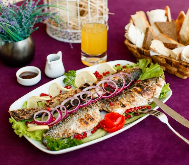 Рыба на гриле с красным луком, помидорами, листьями салата, лимоном и гранатом Бесплатные Фотографии