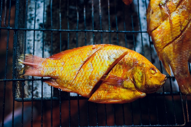 Grilled fish is used on the charcoal grill, a popular food at the evening market in thailand. Premium Photo