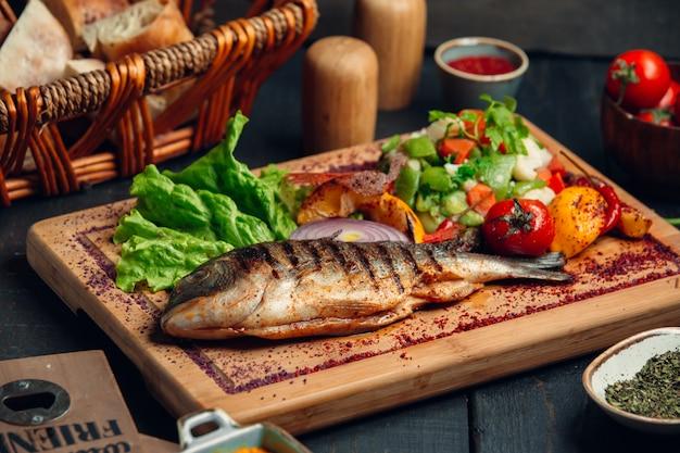 Рыба на гриле с салатом из свежих овощей, листьями салата и сумах Бесплатные Фотографии