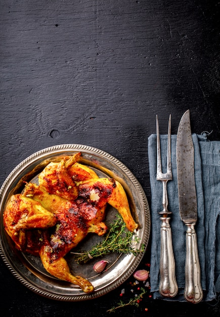 Grilled fried roast chicken tabaka with thyme and garlic Premium Photo