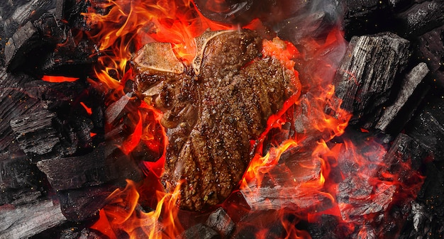Grilled marbled beef steak with coals and smoke Premium Photo