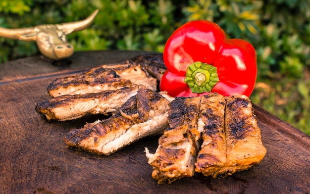 Grilled meat and red pepper on table Free Photo