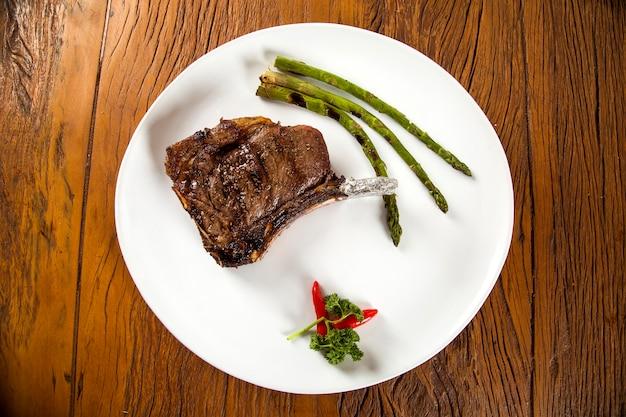 Жареные мясные ребрышки на белой тарелке с помидорами, чесноком и темным острым соусом на борту Premium Фотографии