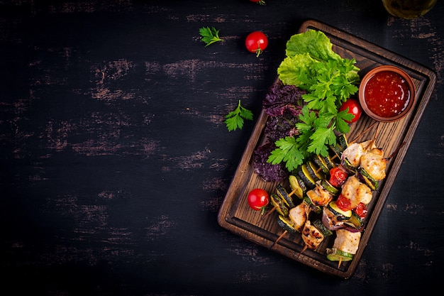 Grilled meat skewers, chicken shish kebab with zucchini, tomatoes and red onions Free Photo