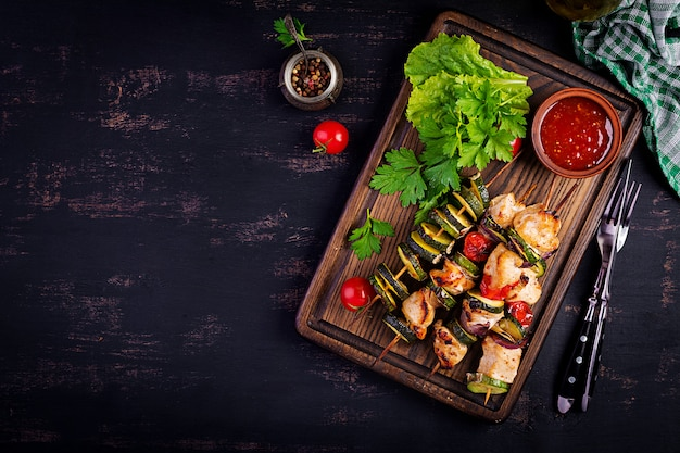 Grilled meat skewers, chicken  shish kebab with zucchini, tomatoes and red onions Premium Photo