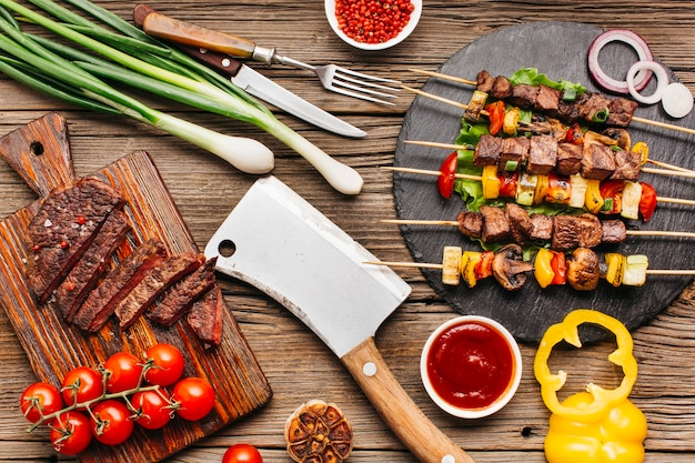 Grilled meat skewers and steak with vegetable on wooden desk Premium Photo