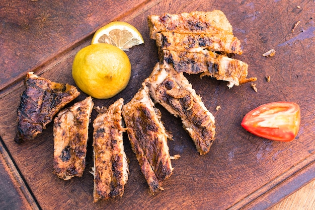 Grilled meat and sliced ​​lemon tomato  on table Free Photo