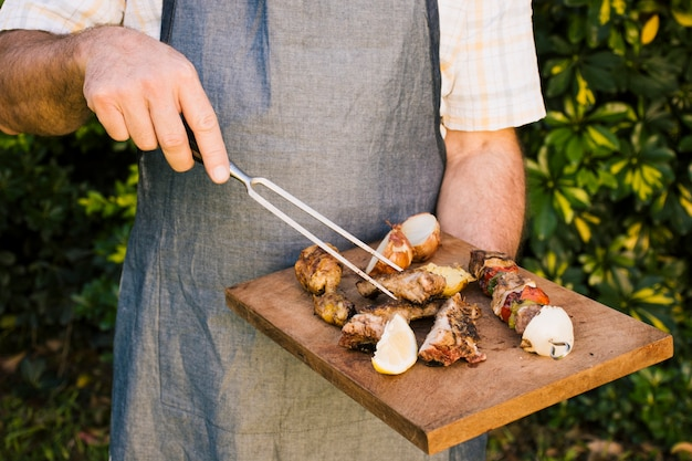 Grilled meat and  tasty vegetables on wooden desk in hands Free Photo