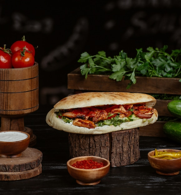Grilled meat and vegetables stuffed inside bread bun served with herbs and sumakh. Free Photo