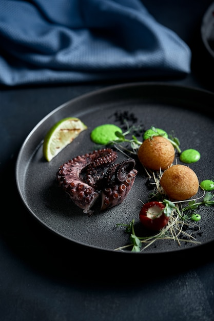 Grilled octopus, low key. copyspace, food fashion , food advertisement. Premium Photo
