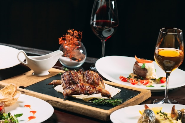 Grilled partridge, sea bass, tartarus.  different dishes on the table in the restaurant. Premium Photo