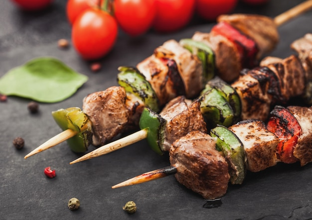 Grilled pork and chicken kebab with paprika on stone chopping board with salt, pepper and tomatoes on black. macro Premium Photo