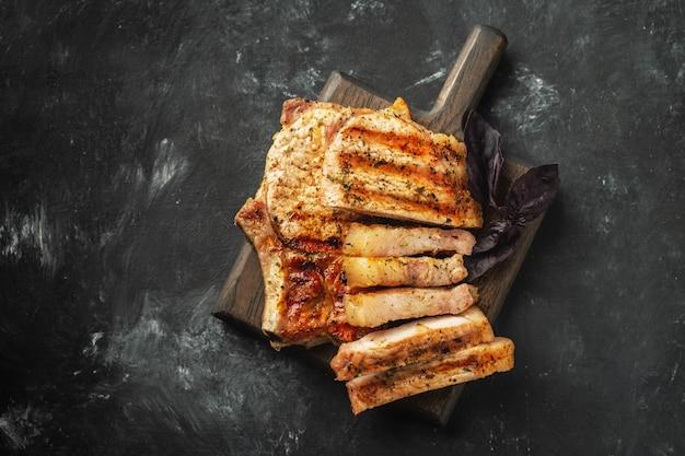 Grilled pork loin on a wooden board on a dark background. Premium Photo