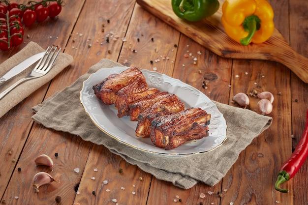 Шашлык из свиных ребрышек на гриле, деревянный фон Premium Фотографии