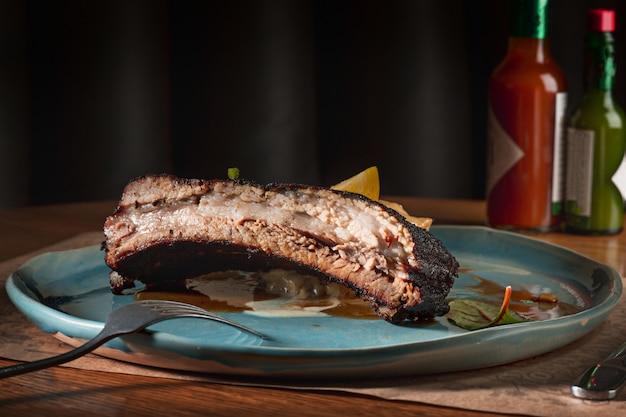 The grilled pork ribs on dark plate on wooden table Free Photo