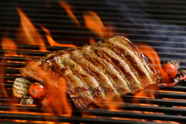 Grilled pork ribs with vegetable on the flaming grill Premium Photo