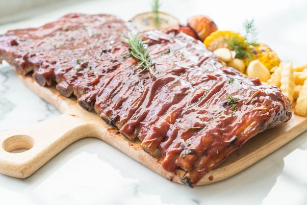 Grilled rib pork with barbecue sauce and vegetable and frech fries on wooden cutting board Free Photo