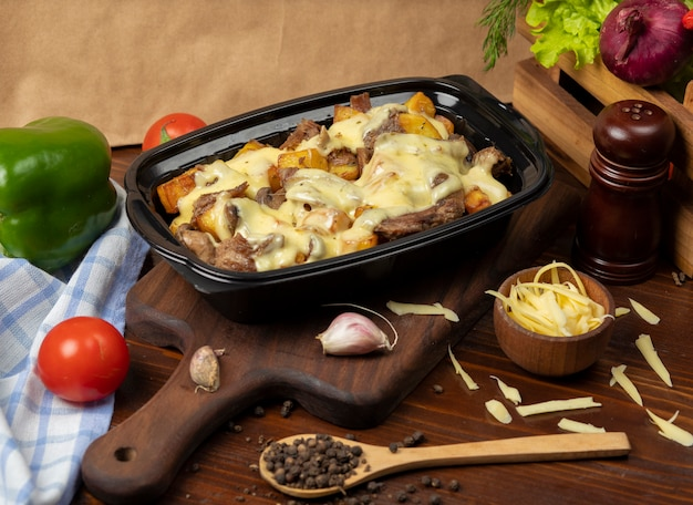 Grilled roasted beef pieces and potato slices in cream melted cheese Free Photo