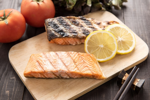 Grilled salmon on cutting board on wooden table. Premium Photo