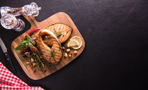 Grilled salmon fish with seasoning and various vegetables on cutting board on black stone Premium Photo